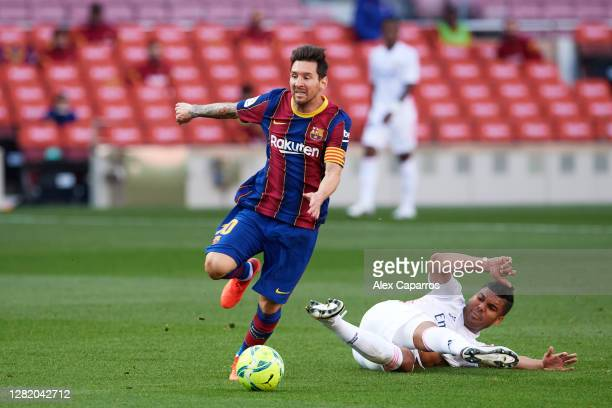 Lionel Messi of FC Barcelona is brought down by Carlos Casemiro of Real Madrid CF during the La Liga Santander match between FC Barcelona and Real...