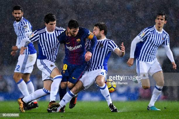 Lionel Messi of FC Barcelona is brought down by Igor Zubeldia and Asier Illarramendi of Real Sociedad de Futbol during the La Liga match between Real...