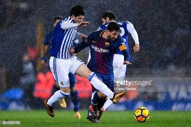 Lionel Messi of FC Barcelona is brought down by Igor Zubeldia and Raul Navas of Real Sociedad de Futbol during the La Liga match between Real...