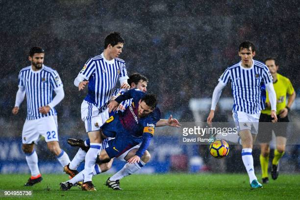 Lionel Messi of FC Barcelona is brought down by Igor Zubeldia and Asier Illarramendi of Real Sociedad de Futbol during the La Liga match between Real...