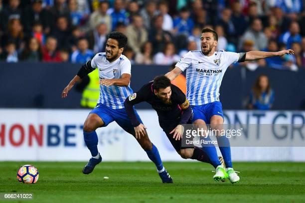 Lionel Messi of FC Barcelona is brought down by Jose Luis Garcia Recio and Ignacio Camacho of Malaga CF during the La Liga match between Malaga CF...