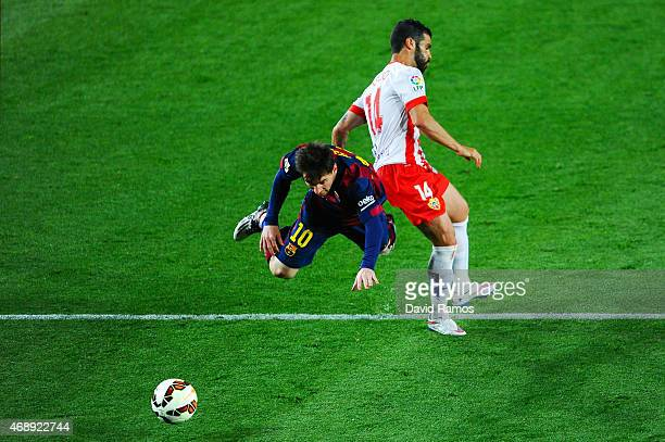 Lionel Messi of FC Barcelona is brought down by Jose Manuel Casado of UD Almeria during the La Liga match between FC Barcelona and UD Almeria at Camp...