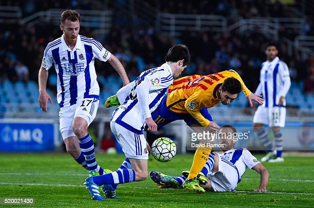 Lionel Messi of FC Barcelona is brought down by Mikel Gonzalez Martinez of Real Sociedad during the La Liga match between Real Sociedad de Futbol and...