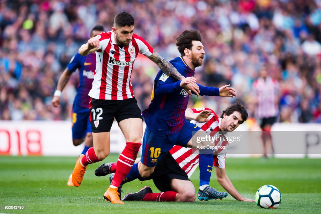 Lionel Messi of FC Barcelona is brought down by Unai Nunez and Mikel San Jose of Athletic Club during the La Liga match between Barcelona and Athletic Club at Camp Nou on March 18, 2018 in Barcelona, Spain.