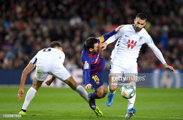 Lionel Messi of FC Barcelona is challenged by German Sanchez and Maxime Gonalons of Granada CF during the La Liga match between FC Barcelona and...