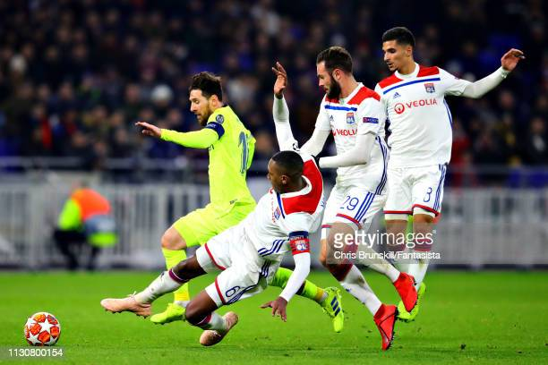 Lionel Messi of FC Barcelona is challenged by Marcelo, Lucas Tousart, and Houssem Aouar all of Olympique Lyonnais during the UEFA Champions League...