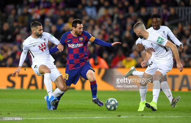 Lionel Messi of FC Barcelona is challenged by Maxime Gonalons and Domingos Duarte of Granada CF during the La Liga match between FC Barcelona and...