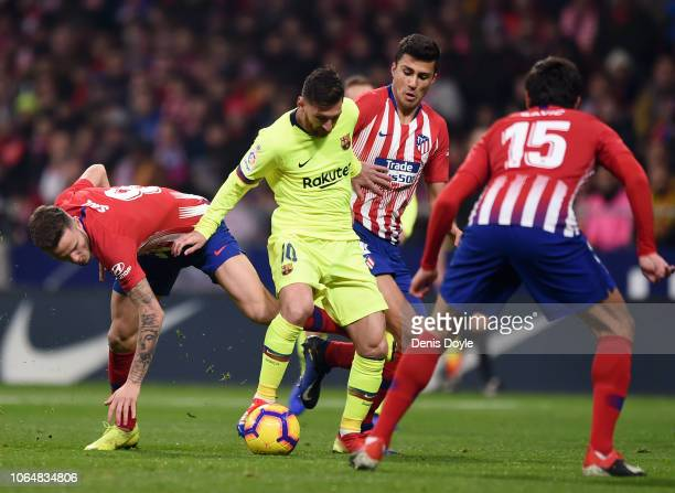 Lionel Messi of FC Barcelona is challenged by Saul Niguez Club Atletico de Madrid during the La Liga match between Club Atletico de Madrid and FC...