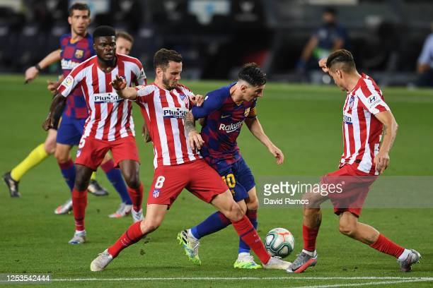 Lionel Messi of FC Barcelona is challenged by Saul Niguez of Atletico Madrid and Jose Maria Gimenez of Atletico Madrid during the Liga match between...