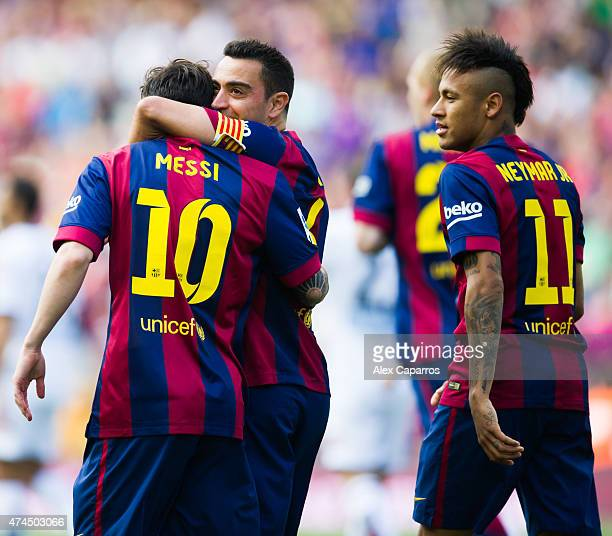 Lionel Messi of FC Barcelona is congratulated by his teammate Xavi Hernandez next to Neymar Santos Jr after scoring the opening goal during the La...