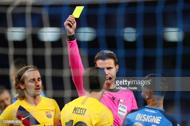 Lionel Messi of FC Barcelona is shown a yellow card by referee Felix Brych during the UEFA Champions League round of 16 first leg match between SSC...