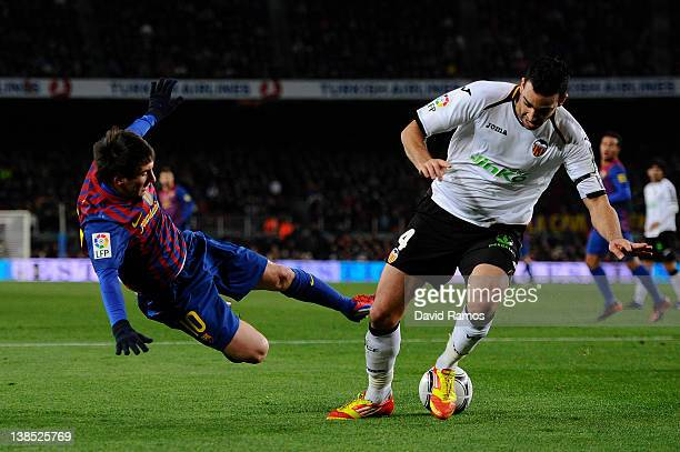 Lionel Messi of FC Barcelona is tackled by Adil Rami of Valencia during the Copa del Rey Semi Final 2nd leg match between FC Barcelona and Valencia...
