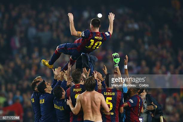 Lionel Messi of FC Barcelona is thrown into the air at the end of the matchby his teammates as they celebrate his new record after he scored three...