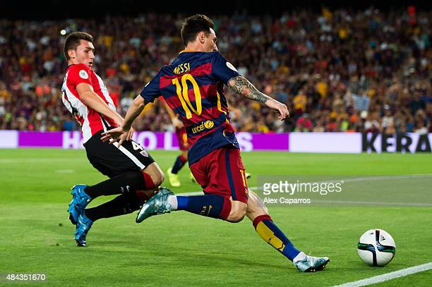 Lionel Messi of FC Barcelona kicks the ball next to Aymeric Laporte of Athletic Club during the Spanish Super Cup second leg match between FC...