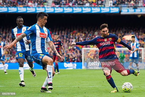 Lionel Messi of FC Barcelona kicks the ball next to Enzo Roco of RCD Espanyol during the La Liga match between FC Barcelona and RCD Espanyol at Camp...