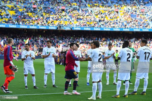 Lionel Messi of FC Barcelona leads the team onto the pitch as they are congratulated by Getafe CF players during the La Liga match between FC...