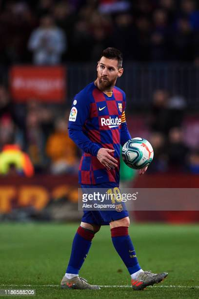 Lionel Messi of FC Barcelona leaves the pitch with the matchball after scoring a hat-trick during the La Liga match between FC Barcelona and RC Celta...