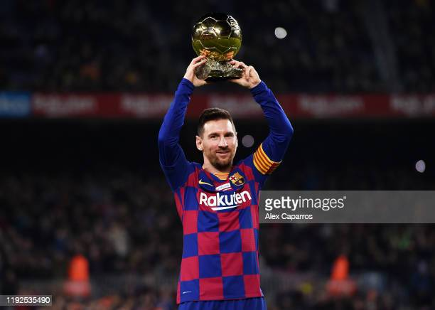 Lionel Messi of FC Barcelona lifts up his sixth Ballon d'Or prior to the Liga match between FC Barcelona and RCD Mallorca at Camp Nou on December 07,...