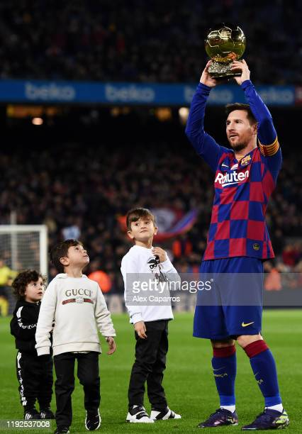 Lionel Messi of FC Barcelona lifts up his sixth Ballon d'Or trophy as his children Ciro Messi Roccuzzo Thiago Messi Roccuzzo and Mateo Messi Roccuzzo...