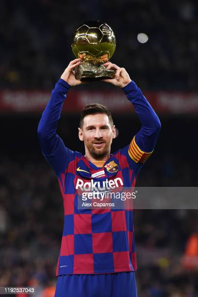 Lionel Messi of FC Barcelona lifts up his sixth Ballon d'Or trophy prior to the Liga match between FC Barcelona and RCD Mallorca at Camp Nou on...