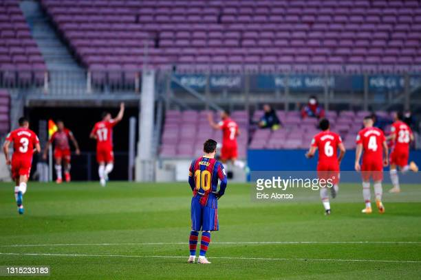 Lionel Messi of FC Barcelona looks dejected as Darwin Machis of Granada CF celebrates with teammates after scoring their team's first goal during the...