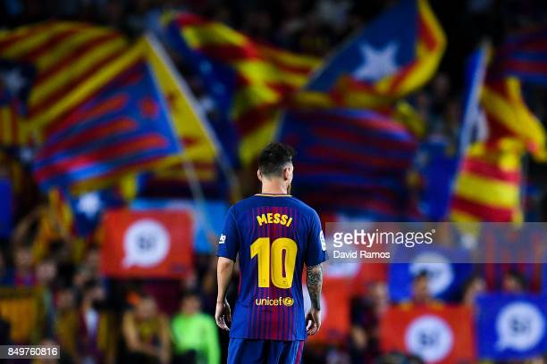 Lionel Messi of FC Barcelona looks on as Catalan Pro-Independence flags are seen on the background during the La Liga match between Barcelona and SD...