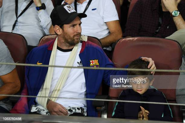 Lionel Messi of FC Barcelona looks on as he sits next to his son Thiago at the stand during the Group B match of the UEFA Champions League between FC...