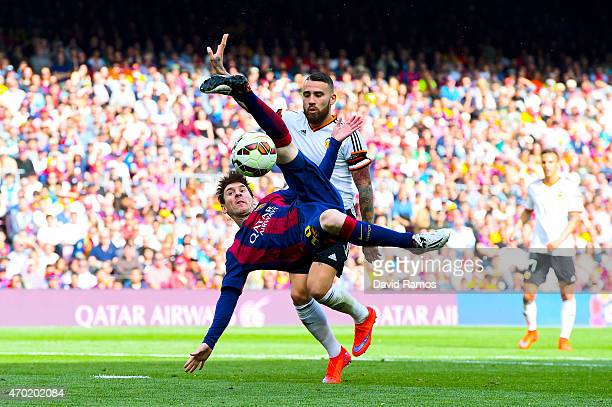 Lionel Messi of FC Barcelona performs an overhead kick under a challenge by Nicolas Otamendi of Valencia CF during the La Liga match between FC...