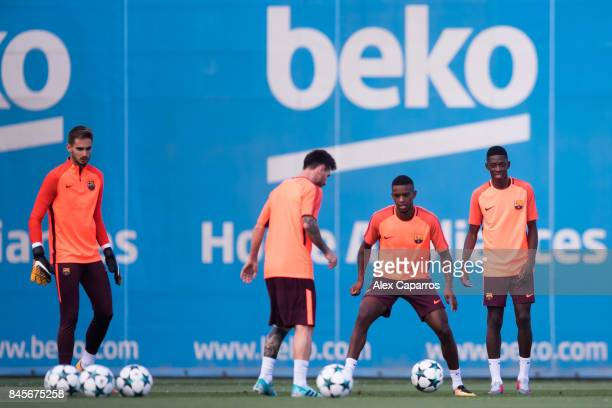 Lionel Messi of FC Barcelona plays the ball next to Nelson Semedo and Ousmane Dembele during a training session ahead of the UEFA Champions League...