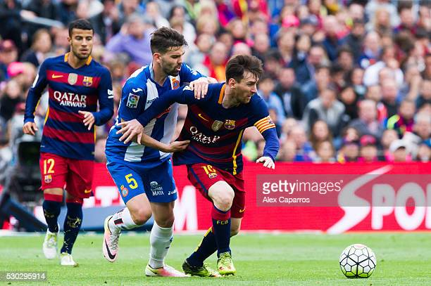 Lionel Messi of FC Barcelona protects the ball from Victor Alvarez of RCD Espanyol during the La Liga match between FC Barcelona and RCD Espanyol at...