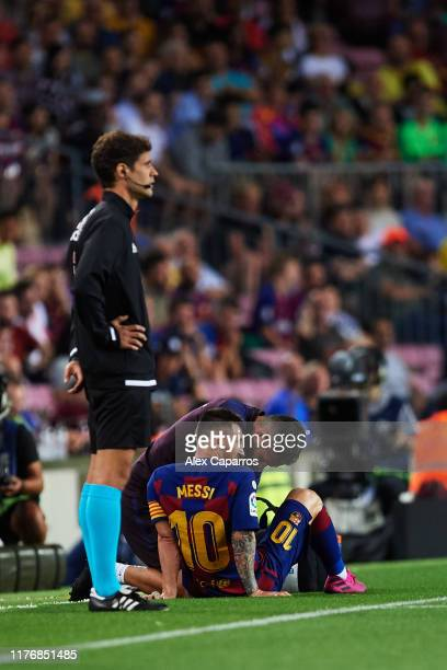 Lionel Messi of FC Barcelona receives medical treatment during the Liga match between FC Barcelona and Villarreal CF at Camp Nou on September 24,...