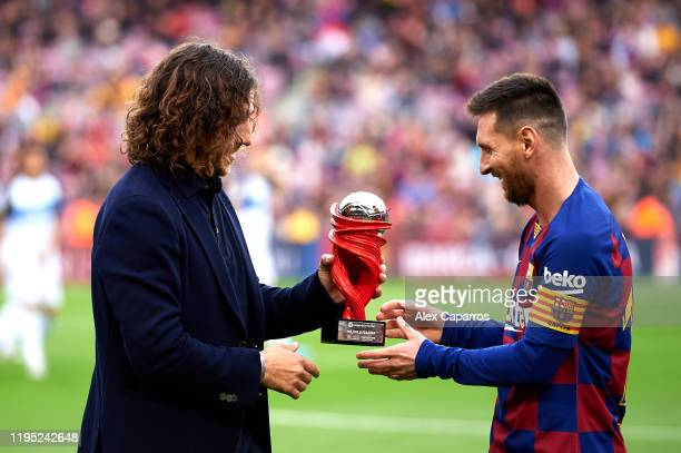 Lionel Messi of FC Barcelona receives the trophy as best player of November in the Spanish La Liga from Carles Puyol before the La Liga match between...