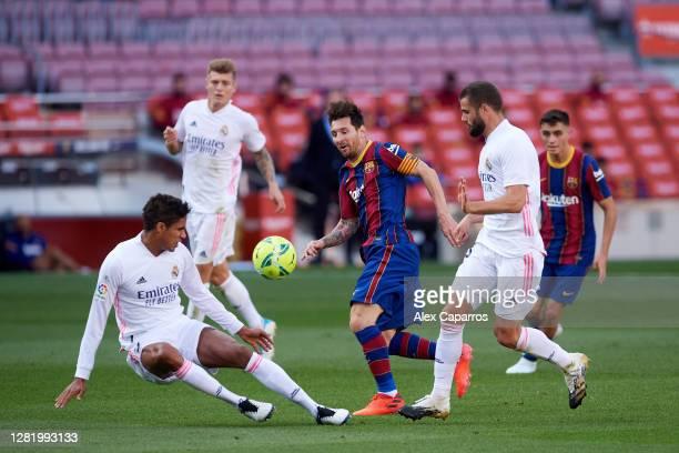 Lionel Messi of FC Barcelona runs with the ball amongst Raphael Varane and Nacho Fernandez of Real Madrid CF during the La Liga Santander match...