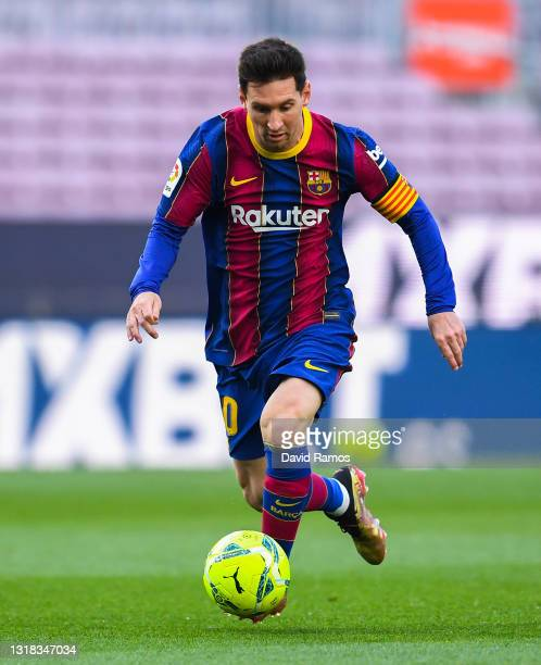 Lionel Messi of FC Barcelona runs with the ball during the La Liga Santander match between FC Barcelona and RC Celta at Camp Nou on May 16, 2021 in...