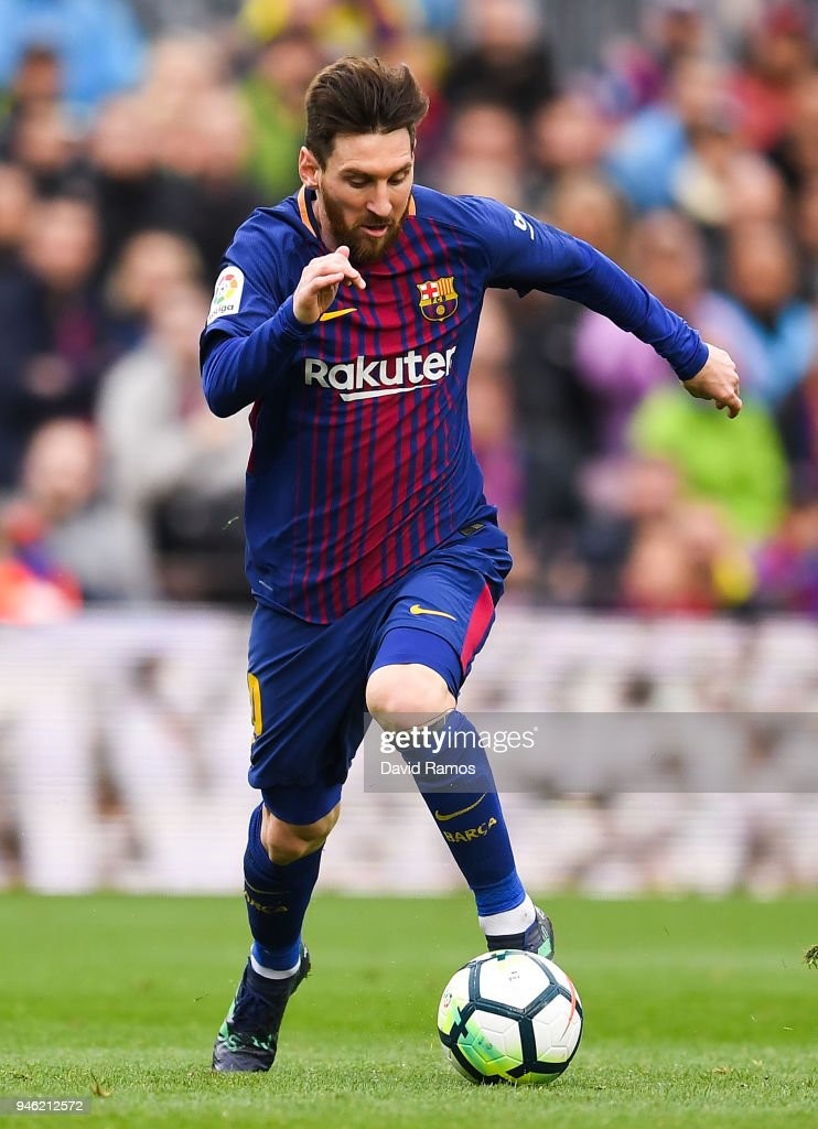 Lionel Messi of FC Barcelona runs with the ball during the La Liga match between Barcelona and Valencia at Camp Nou on April 14, 2018 in Barcelona, Spain.