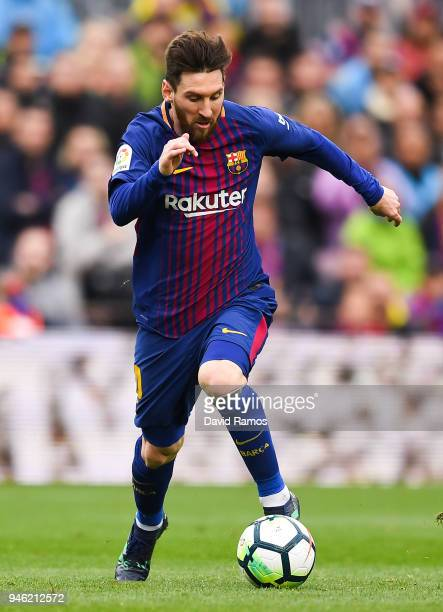 Lionel Messi of FC Barcelona runs with the ball during the La Liga match between Barcelona and Valencia at Camp Nou on April 14 2018 in Barcelona...