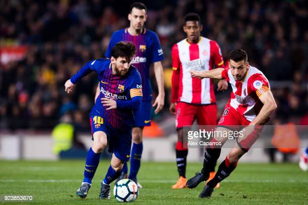 Lionel Messi of FC Barcelona runs with the ball next to Alex Granell of Girona FC during the La Liga match between Barcelona and Girona at Camp Nou...