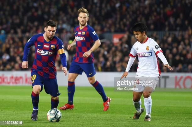 Lionel Messi of FC Barcelona runs with the ball under pressure from Takefusa Kubo of RCD Mallorca during the Liga match between FC Barcelona and RCD...