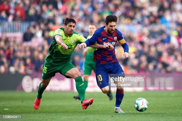Lionel Messi of FC Barcelona runs with the ball under pressure from Jose Angel Valdes 'Cote' of SD Eibar during the La Liga match between FC...