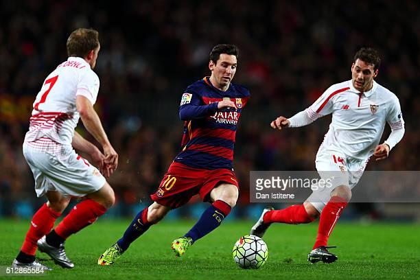 Lionel Messi of FC Barcelona runs with the ball under pressure from Michael KrohnDehli and Sebastian Cristoforo of Sevilla FC during the La Liga...