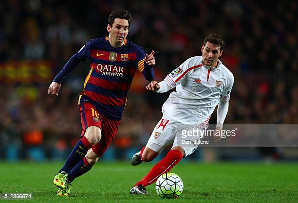 Lionel Messi of FC Barcelona runs with the ball under pressure from Sebastian Cristoforo of Sevilla FC during the La Liga match between FC Barcelona...