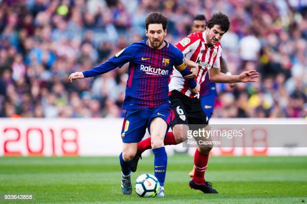 Lionel Messi of FC Barcelona runs with the ball under pressure from Mikel San Jose of Athletic Club during the La Liga match between Barcelona and...