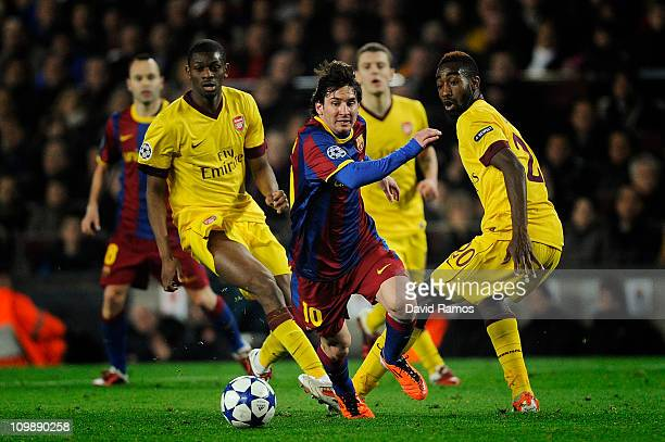 Lionel Messi of FC Barcelona runs with the balls under a challenge by Abou Diaby and Johan Djourou of Arsenal during the UEFA Champions League round...