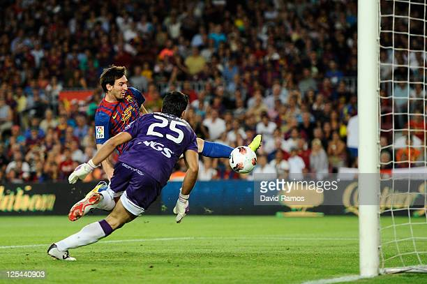 Lionel Messi of FC Barcelona scores his first goal under a challenge by Andres Fernandez Moreno of CA Osasuna during the La Liga soccer match between...