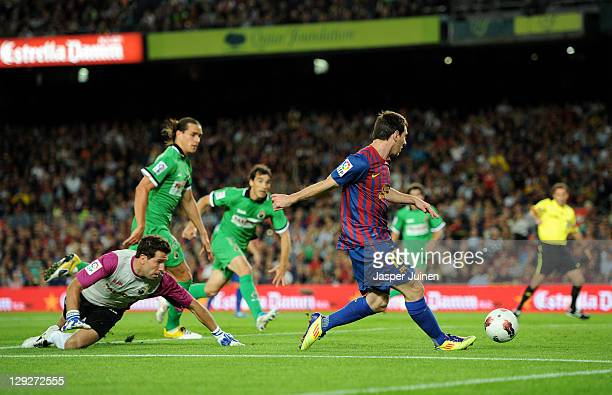 Lionel Messi of FC Barcelona scores his sides opening goal past goalkeeper Antonio Martinez of Racing Santander during the la Liga match between FC...