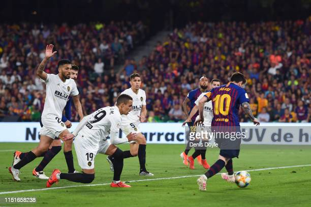 Lionel Messi of FC Barcelona scores his team's first goal during the Spanish Copa del Rey match between Barcelona and Valencia at Estadio Benito...