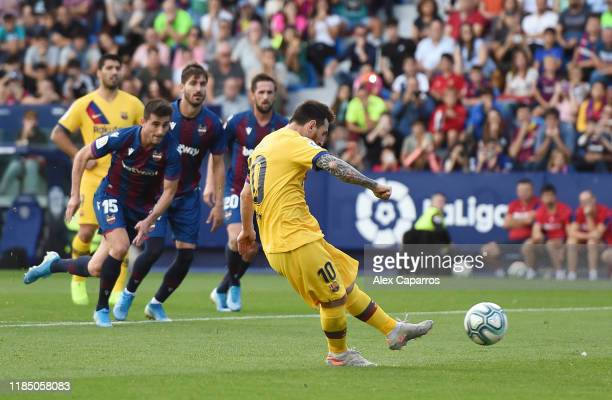 Lionel Messi of FC Barcelona scores his team's first goal during the Liga match between Levante UD and FC Barcelona at Ciutat de Valencia on November...