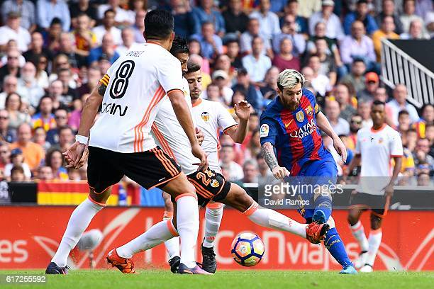 Lionel Messi of FC Barcelona scores his team's first goal during the La Liga match between Valencia CF and FC Barcelona at Mestalla stadium on...