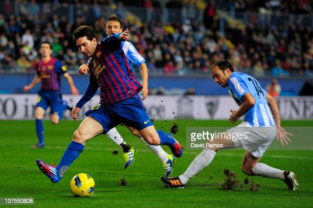 Lionel Messi of FC Barcelona scores his team's fourth goal during the La Liga match between Malaga CF and FC Barcelona at Rosaleda Stadium on January...