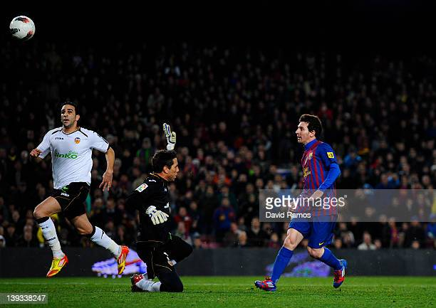Lionel Messi of FC Barcelona scores his team's fourth goal under a challenge by Diego Alves of Valencia CF during the La Liga match between FC...
